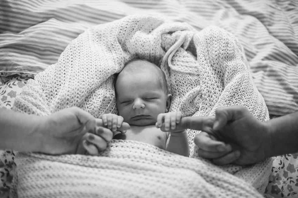 Mikuláš se pevně drží prstů svých rodičů