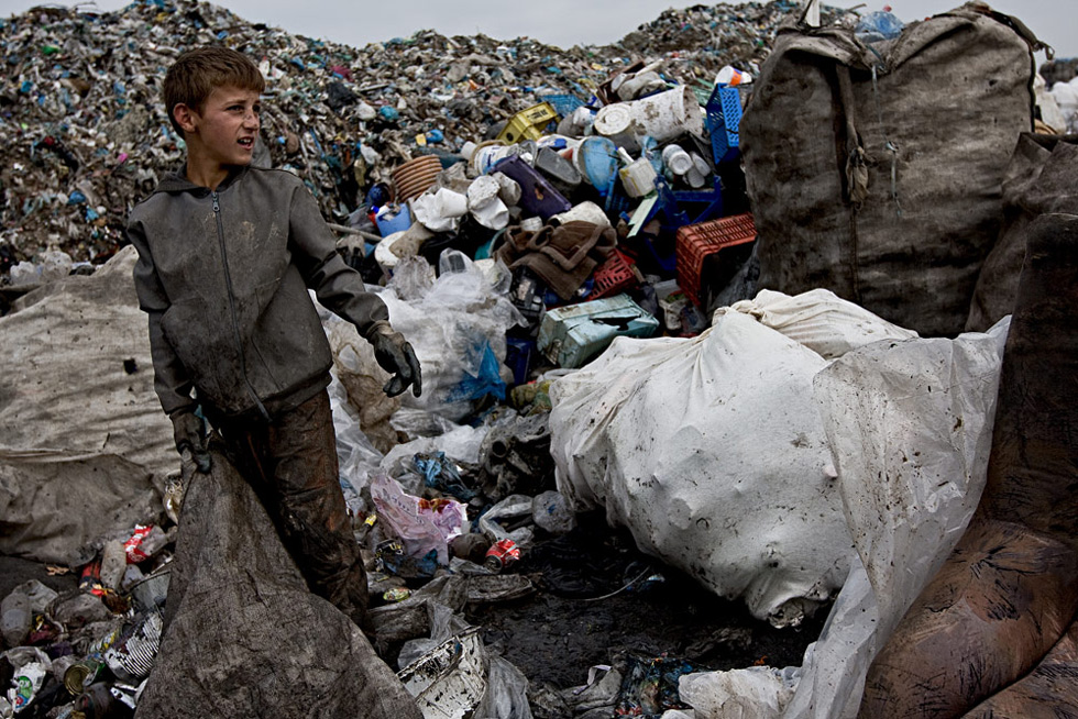 Chlapec třídí odpad na skládce