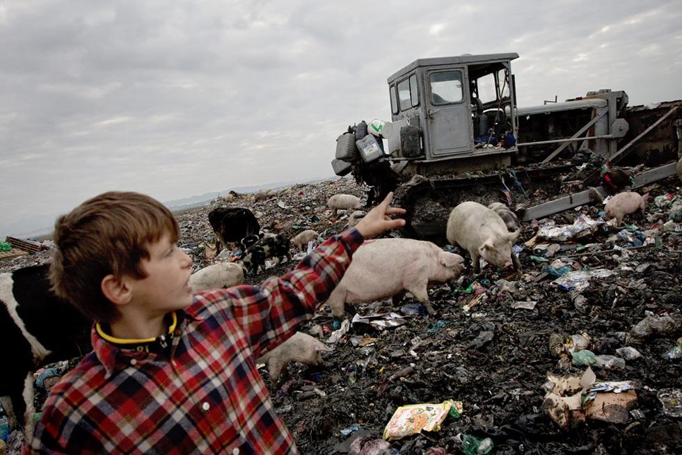 Chlapec ukazuje na bagr na skládce