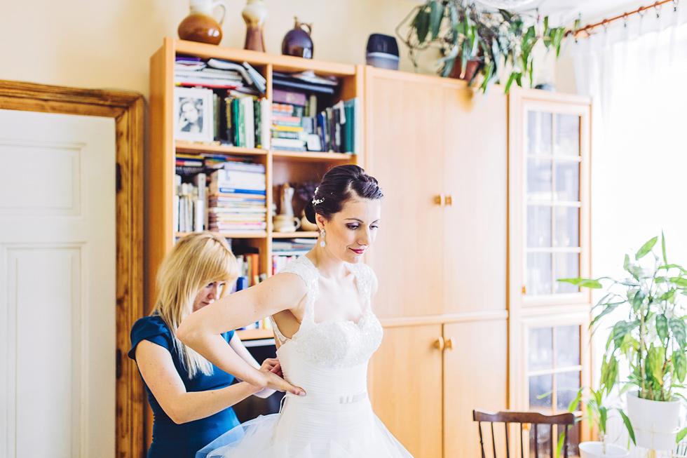 Kamarádka obléká nevěstě svatební šaty