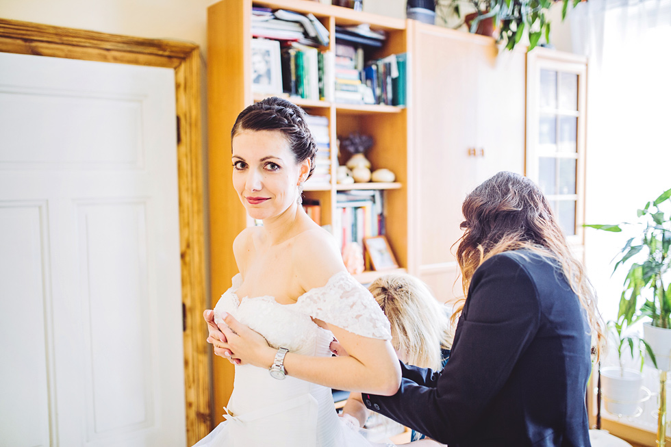 Nevěstě oblékají svatební šaty