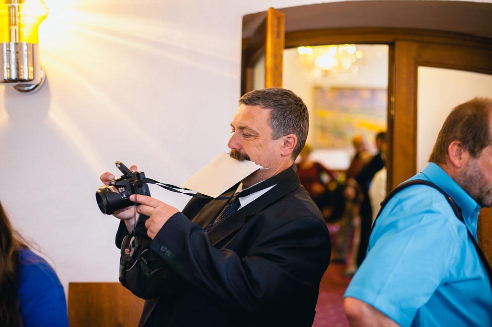 Pán drží zubama obálku na vítání občánků