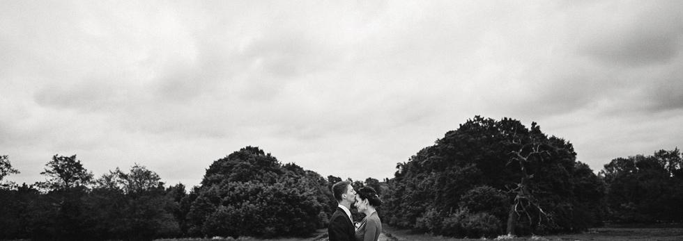 Ženich líbá nevěstu na čelo u lesa