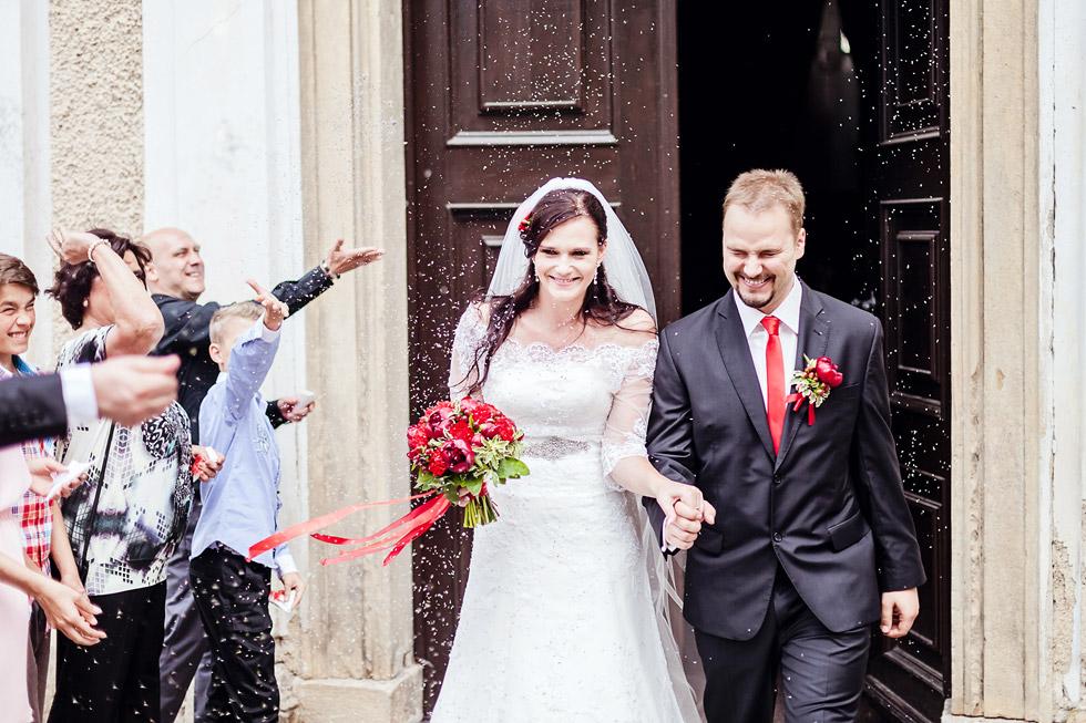 Nevěsta a ženich vycházejí z kostela