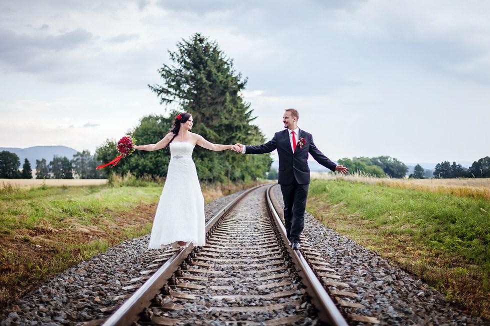 Novomanželé jdou po kolejích