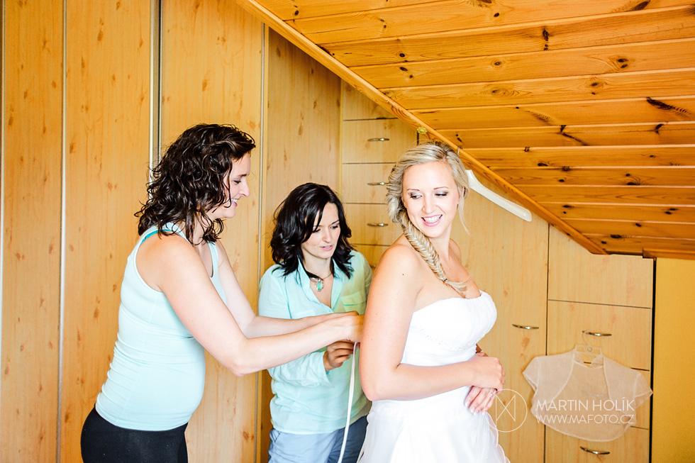 Kamarádky oblékají nevěstě svatební šaty
