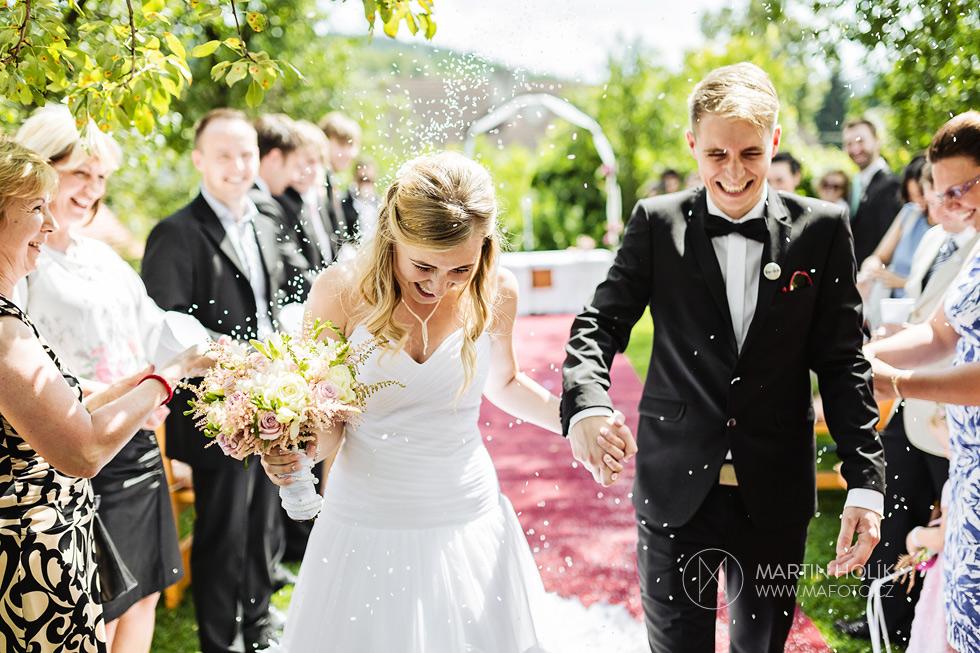 Nevěsta a ženich odcházejí od oltáře zasypáni rýží