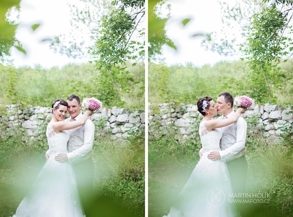 Nevěsta a ženich se něžně líbají u zídky