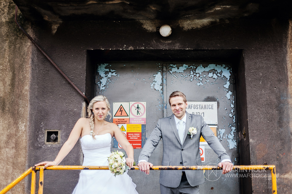 Nevěsta a ženich se opírají o zábradlí