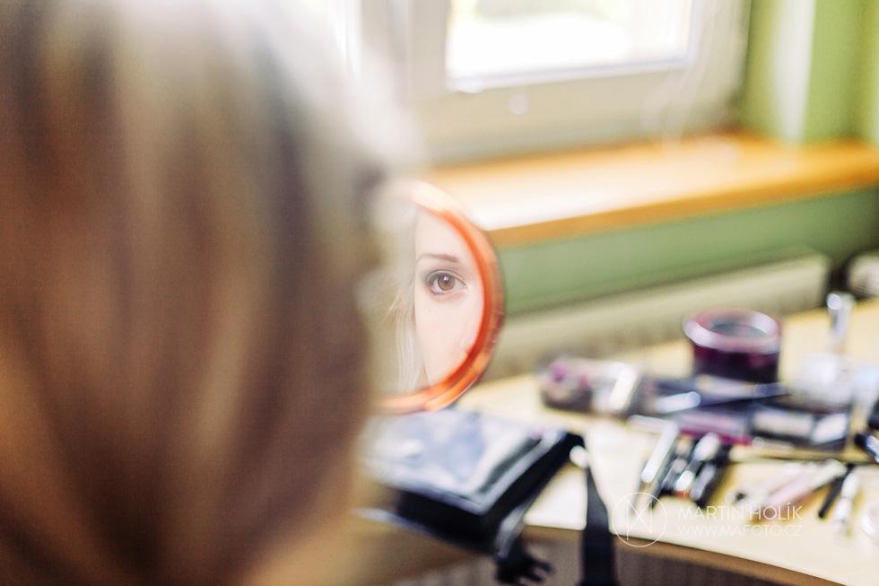 Nevěsta se dívá do zrcadla při líčení