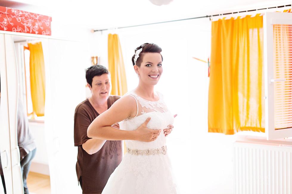 Nevěsta si obléká svatební šaty
