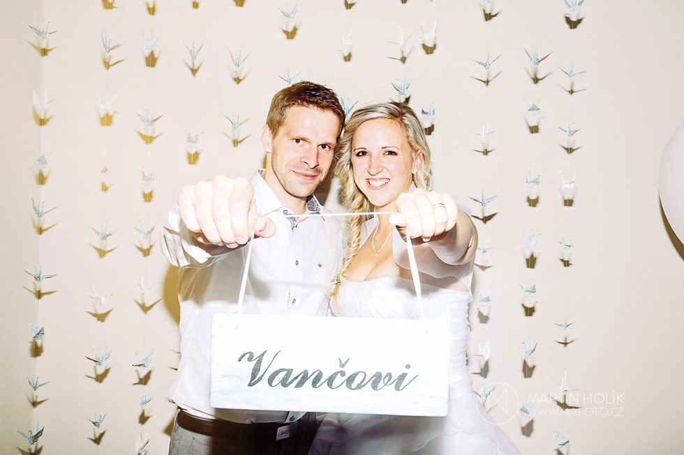 Novomanželé a jejich cedule ve fotokoutku