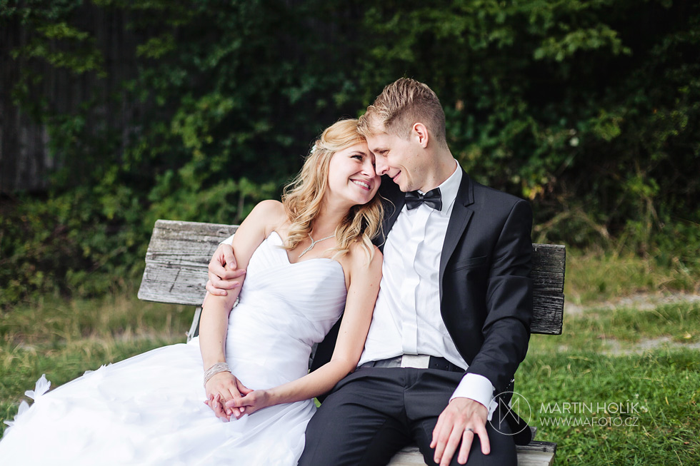 Novomanželé sedí na lavičce