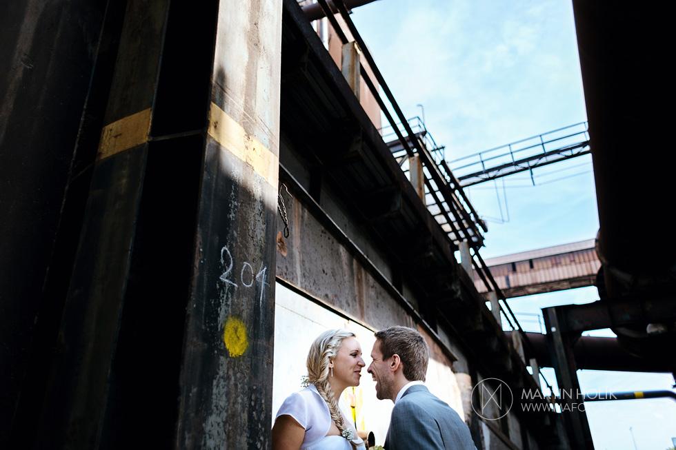 Ženich škádlí nevěstu v industriálním areálu železáren