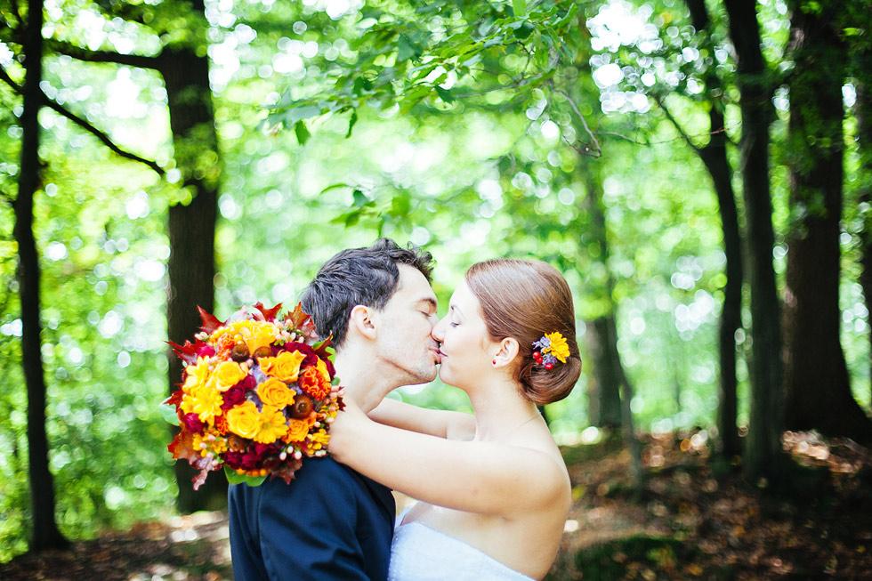 Nevěsta a ženich se líbají v lese