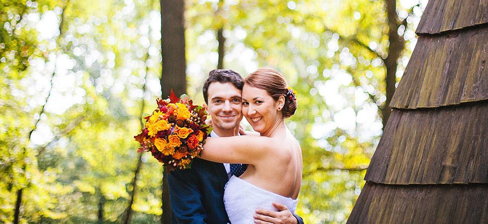 Nevěsta a ženich pózují na svatební fotografii v podzimním lese