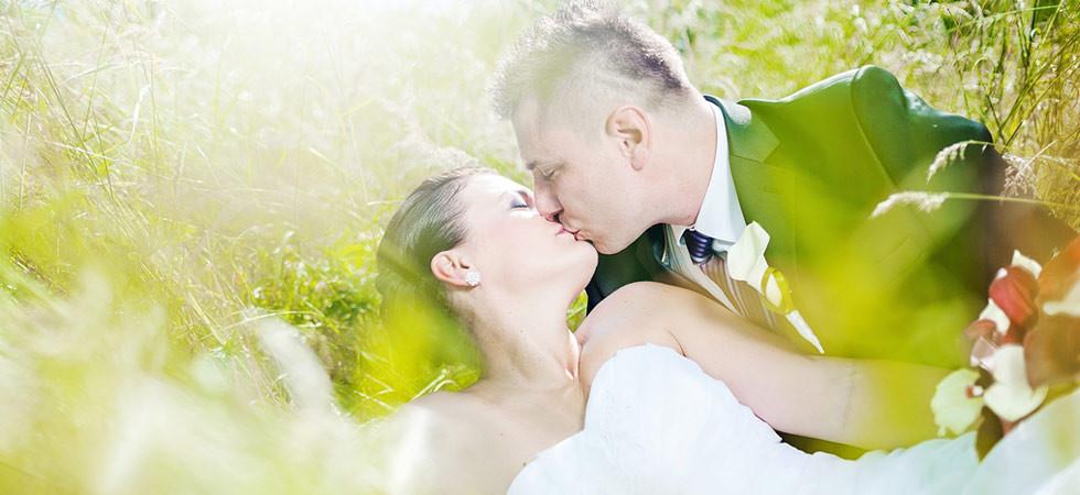Nevěsta leží v trávě a ženich ji něžně líbá