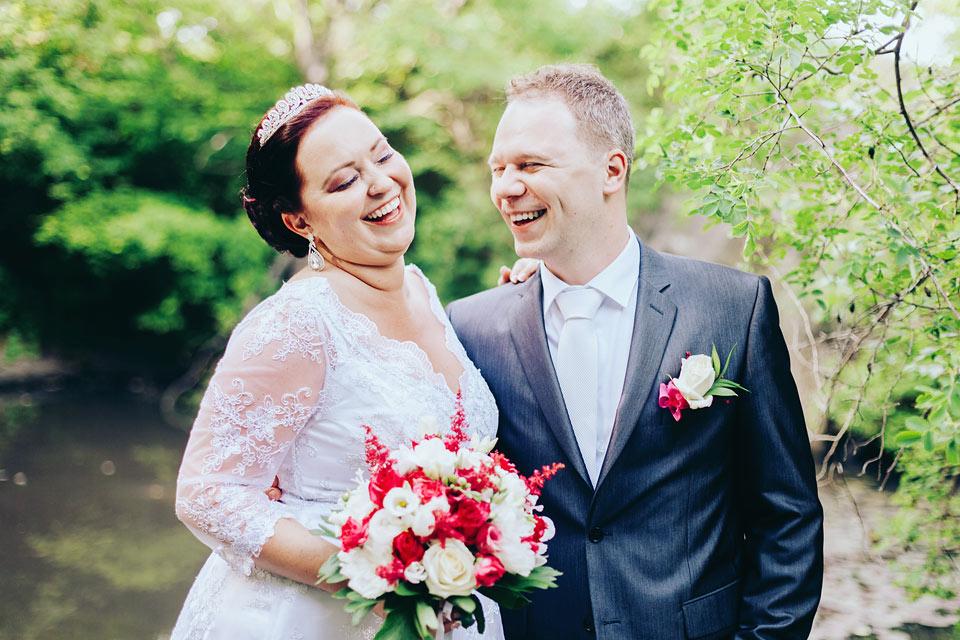 Fotografie smějící se nevěsty a ženicha u jezírka