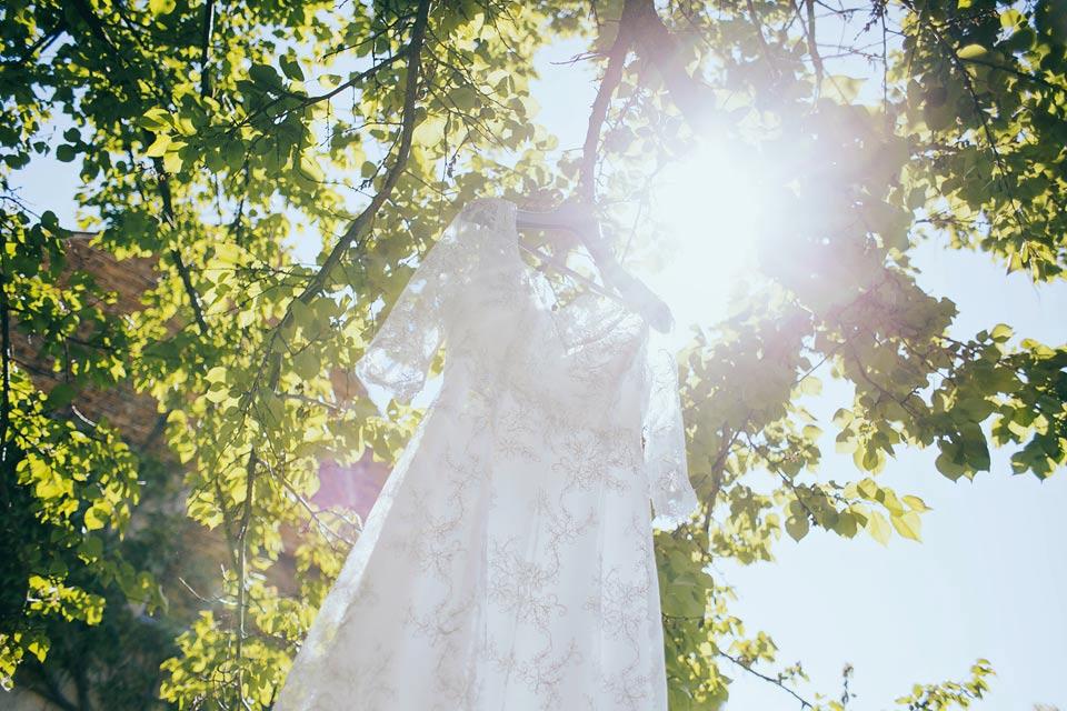 Fotografie svatebních šatů pověšených na stromě