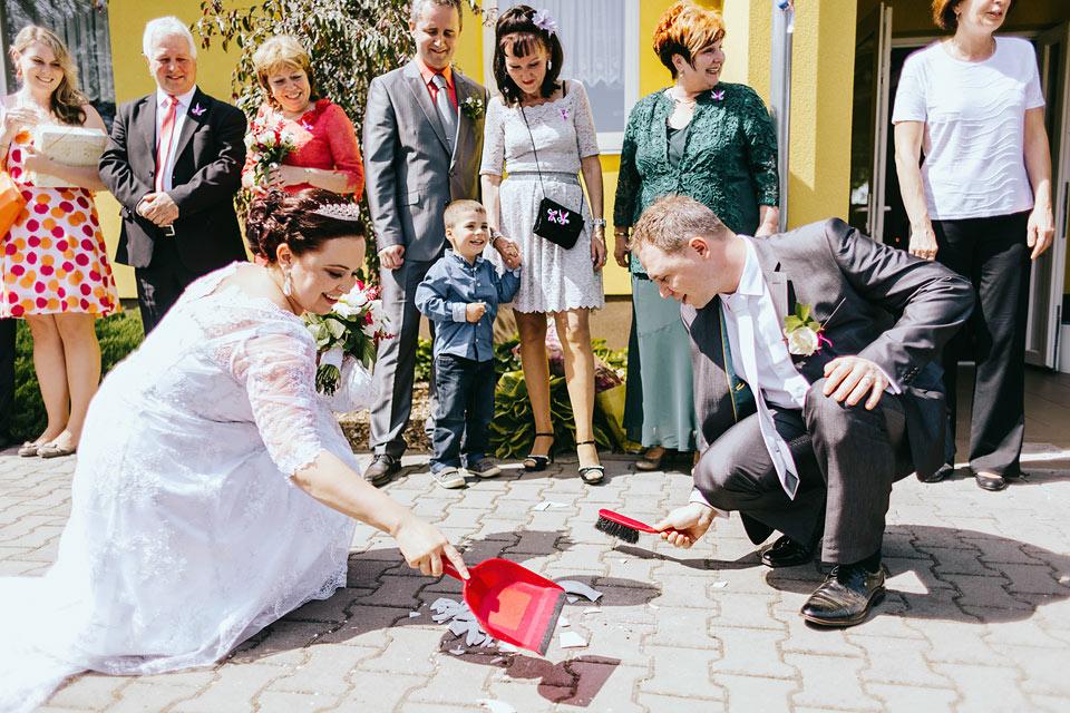 Nevěsta a ženich zametají střepy ze svatebního talířku