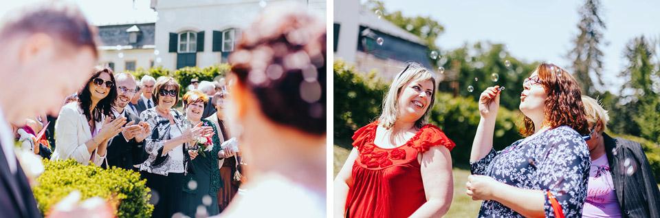 Svatební hosté tleskají nevěstě a ženichovi