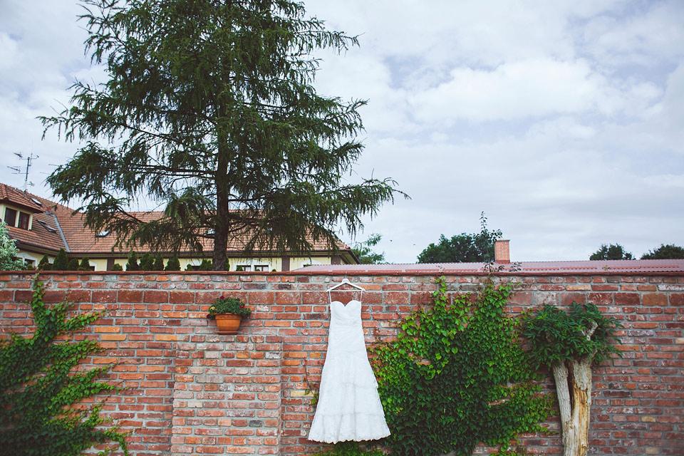 fotografie svatebních šatů na cihlové stěně