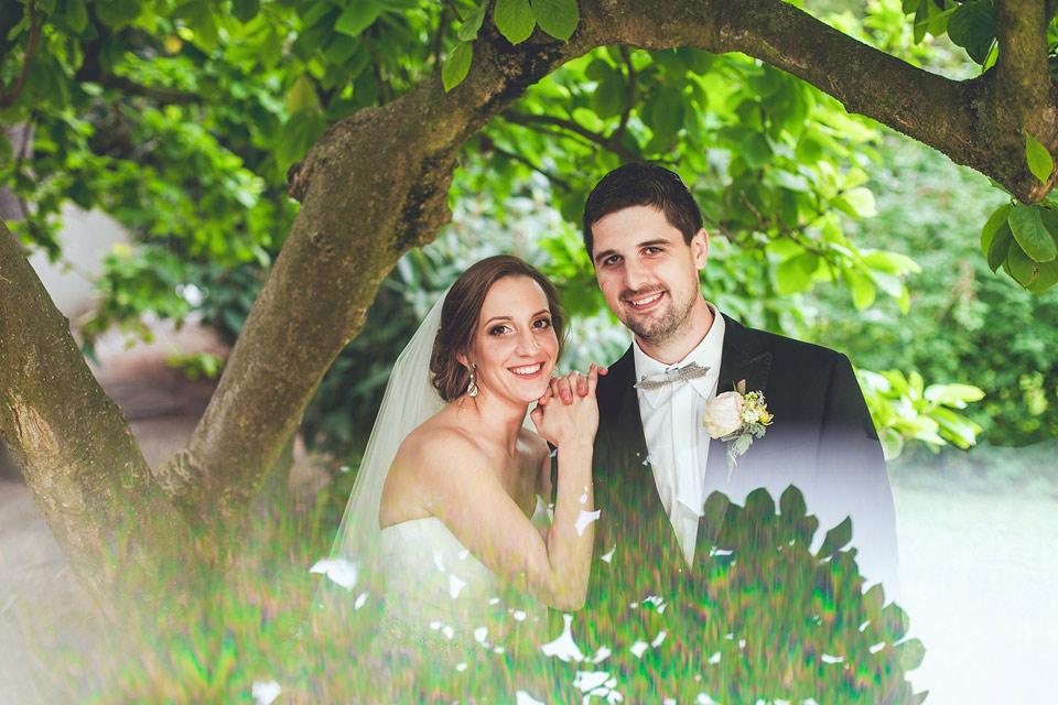 Nevěsta a ženich pózují pod větví