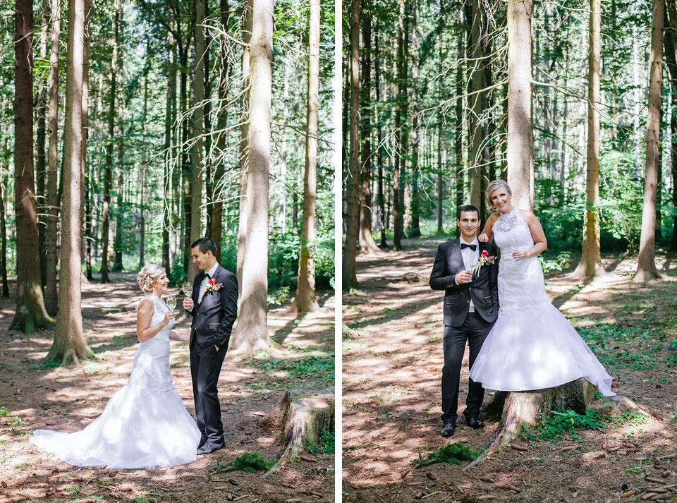 Nevěsta a ženich pózují s vínem v lese