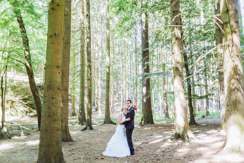 Nevěsta pozuje s ženichem v lese