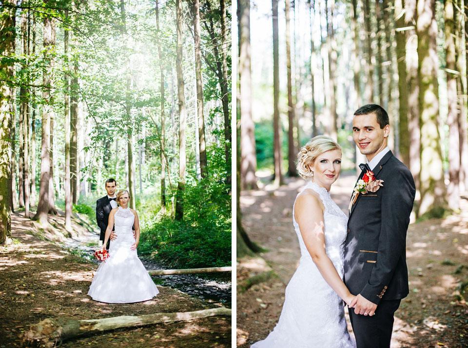 Ženich a nevěsta pózují svatebnímu fotografovi v lese
