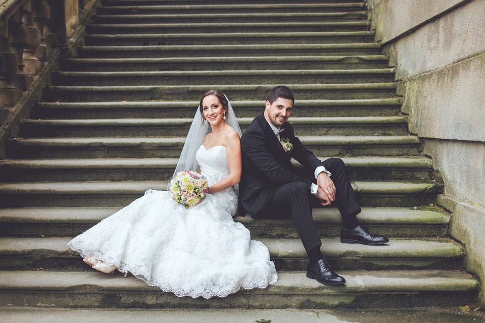 ženich a nevěsta sedí na schodišti