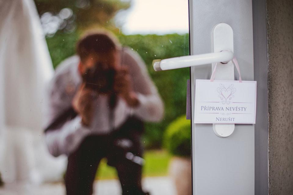 Fotografie fotografa odrážejícího se ve dveřích