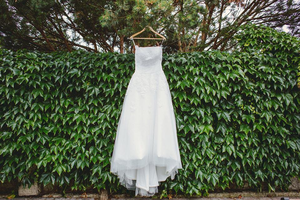 Fotografie svatebních šatů zavěšených na borovici