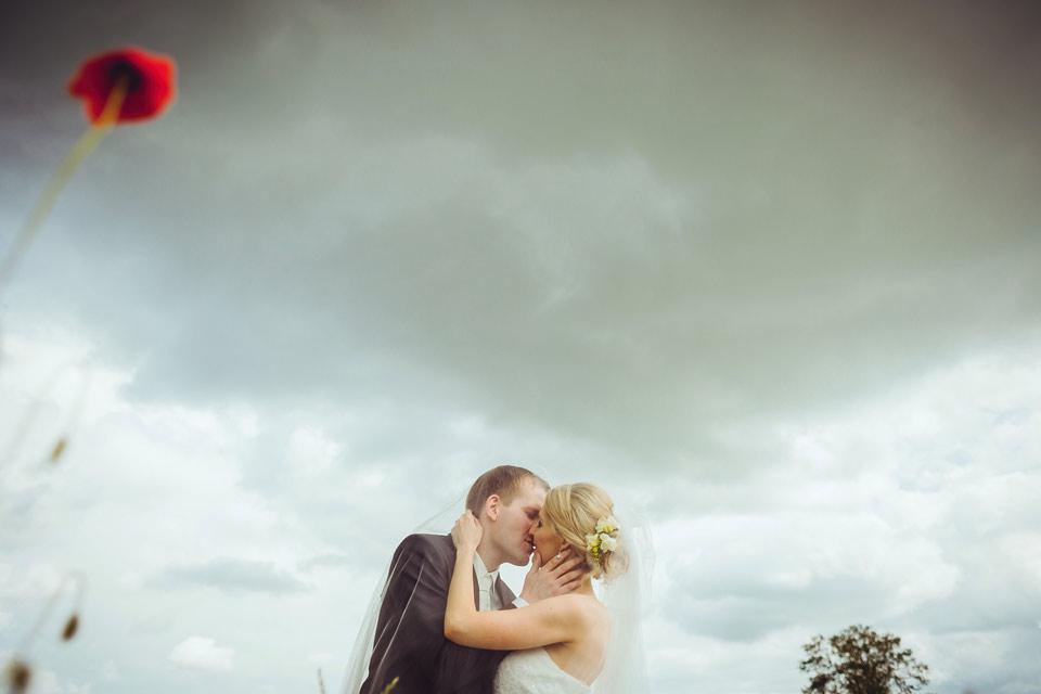 Ženich líbá nevěstu přímo pod bouřkovým mrakem