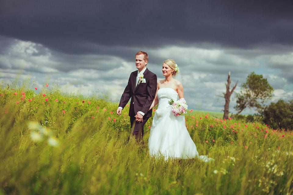 Nevěsta a ženich se procházejí po polní cestě