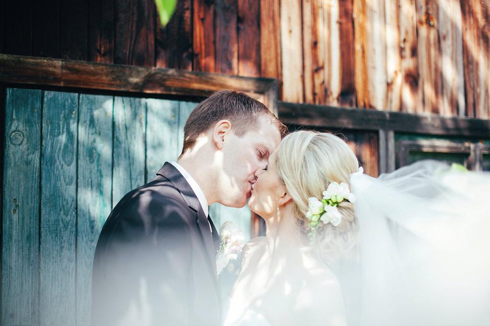 Nevěsta líbá ženicha u chaloupky