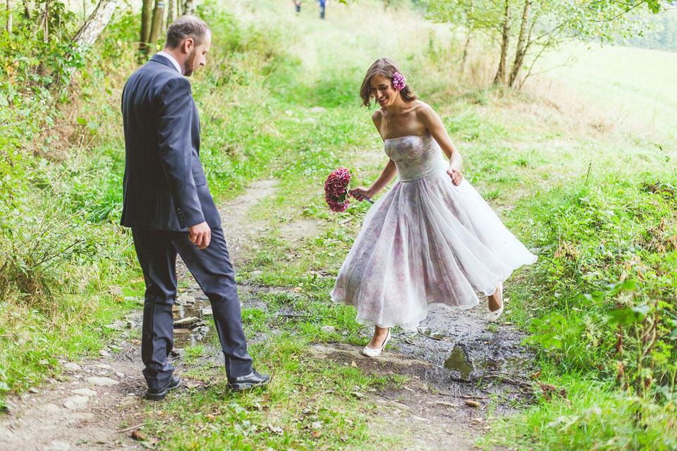 Nevěsta přeskakuje louži na lesní cestě