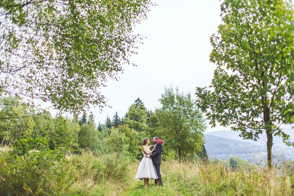 Portrét nevěsty a ženicha na lesní cestě