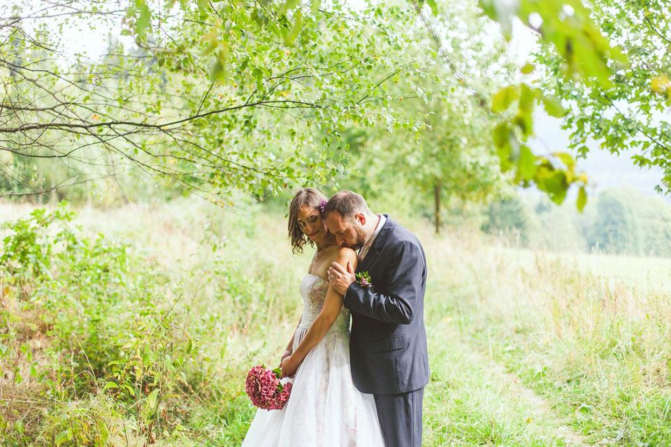 Ženich líbá nevěstu na rameno