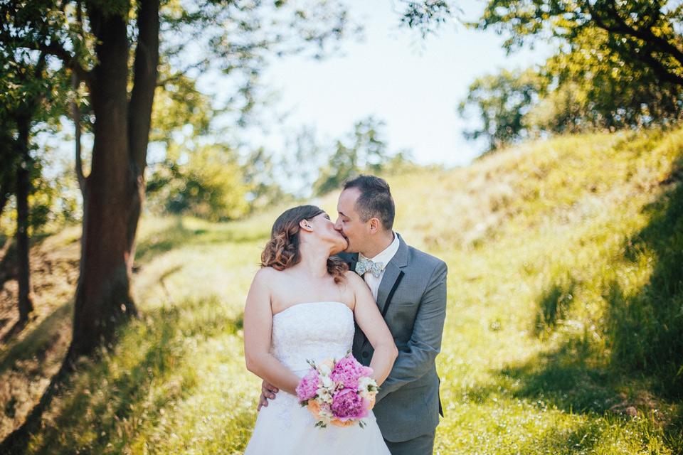Fotka polibku nevěsty ženichem v sadu