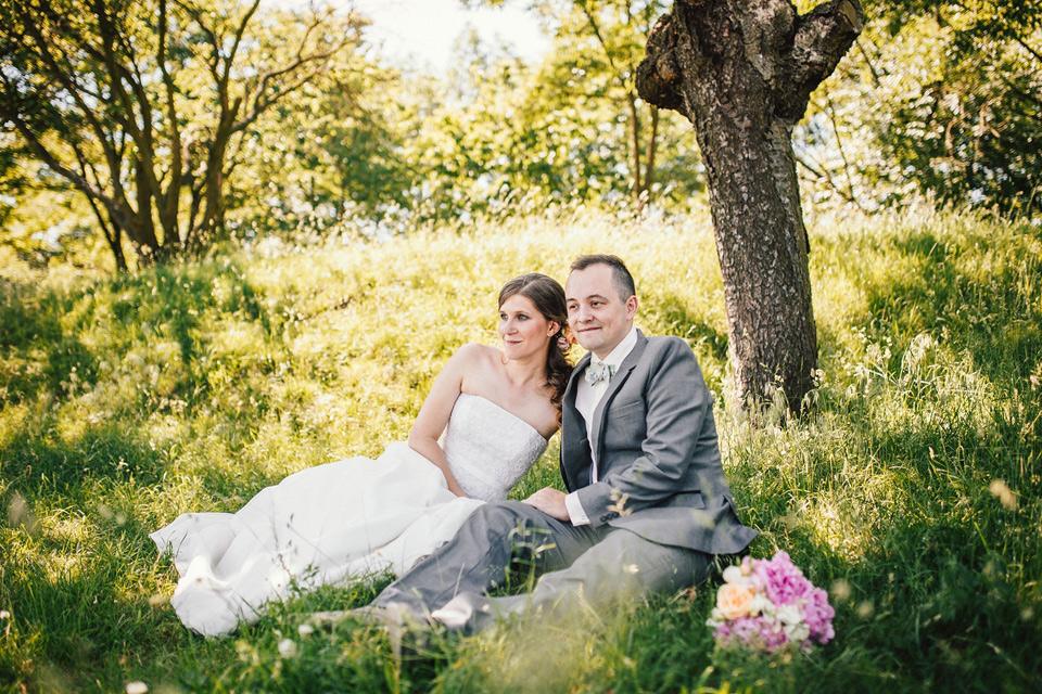 Fotka ženicha a nevěsty v sadu v trávě