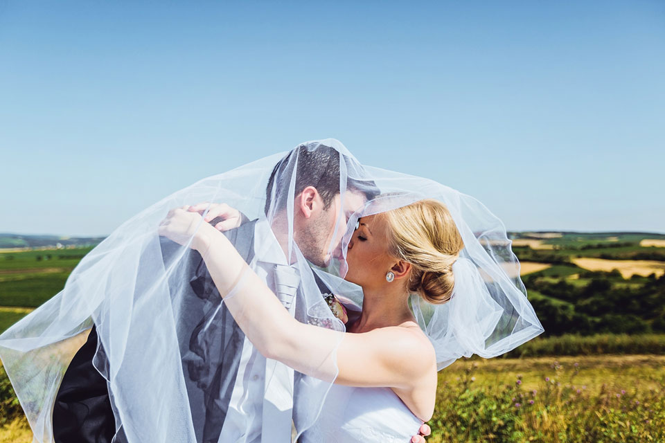 Fotografie nevěsty líbající ženicha pod závojem