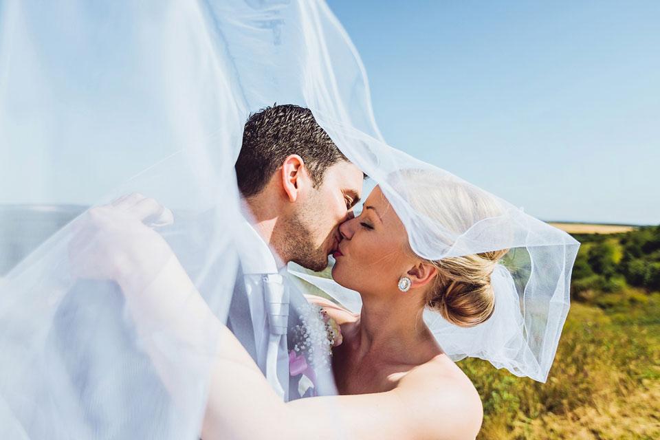 Fotografie svatební líbačky pod závojem