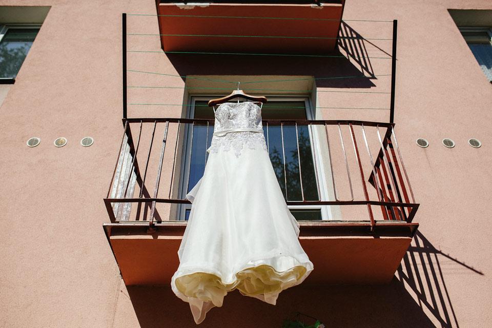 Fotografie svatebních šatů zavěšených na balkóně