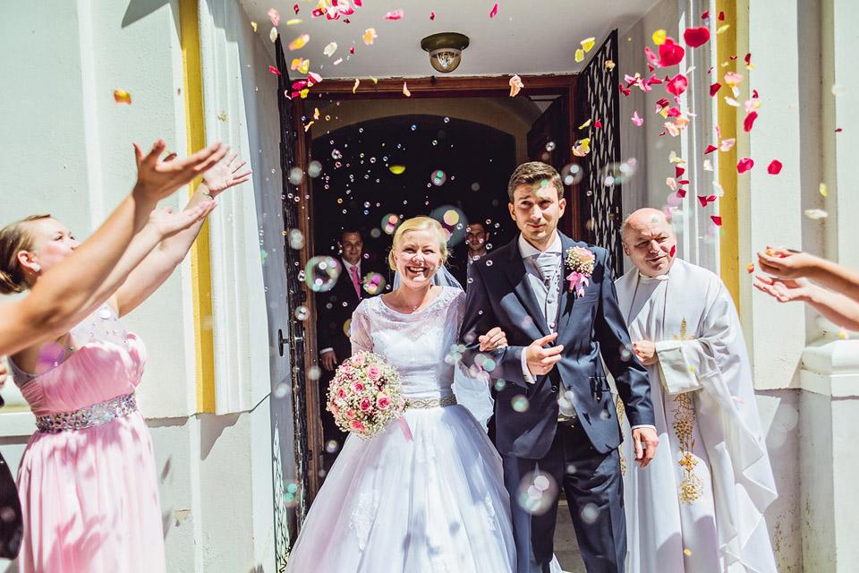 Nevěsta a ženich vycházejí z kostelu
