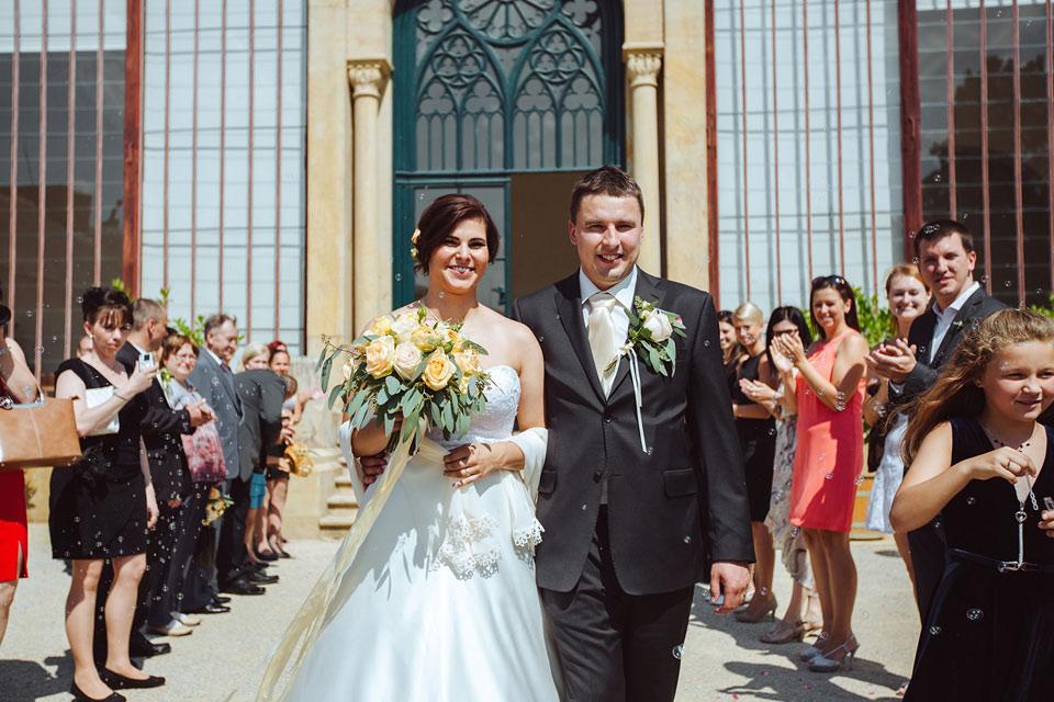 Novomanželé vycházejí z místa obřadu