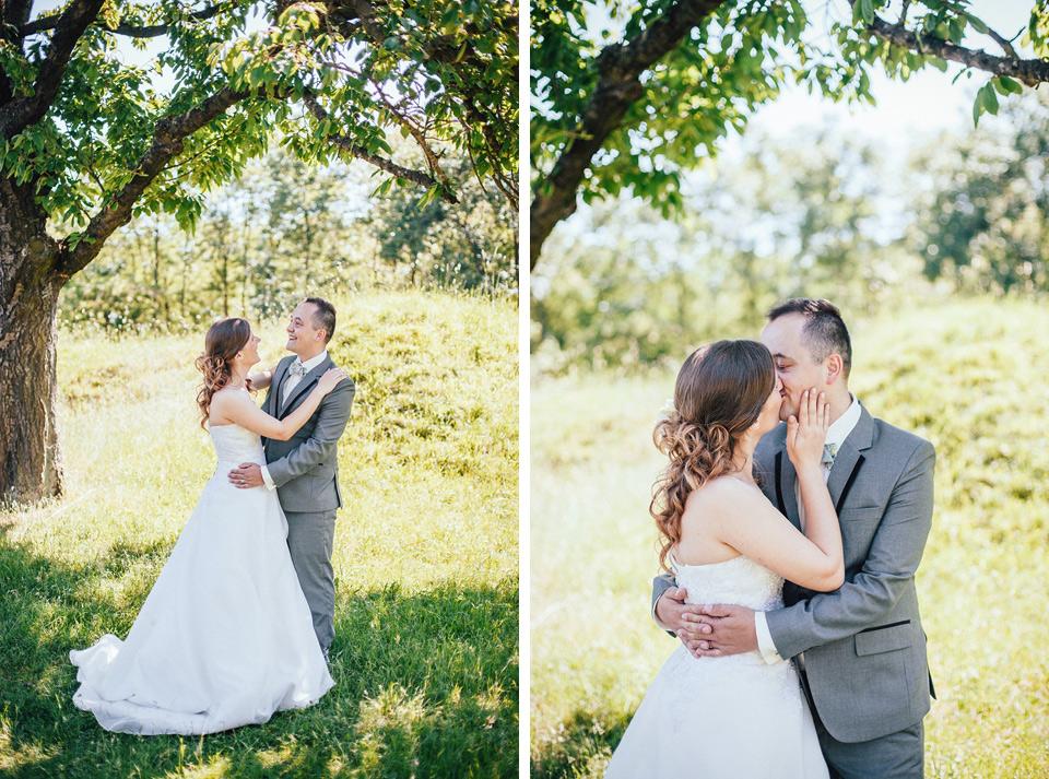 Romantický polibek mezi stromy v sadu
