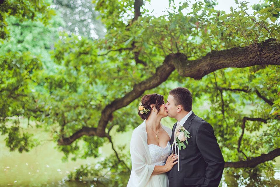 Romantický polibek nevěsty a ženicha u rybníka