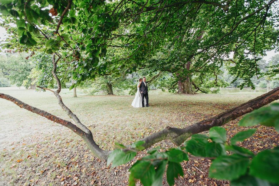 Svatební portrét v parku pod stromy