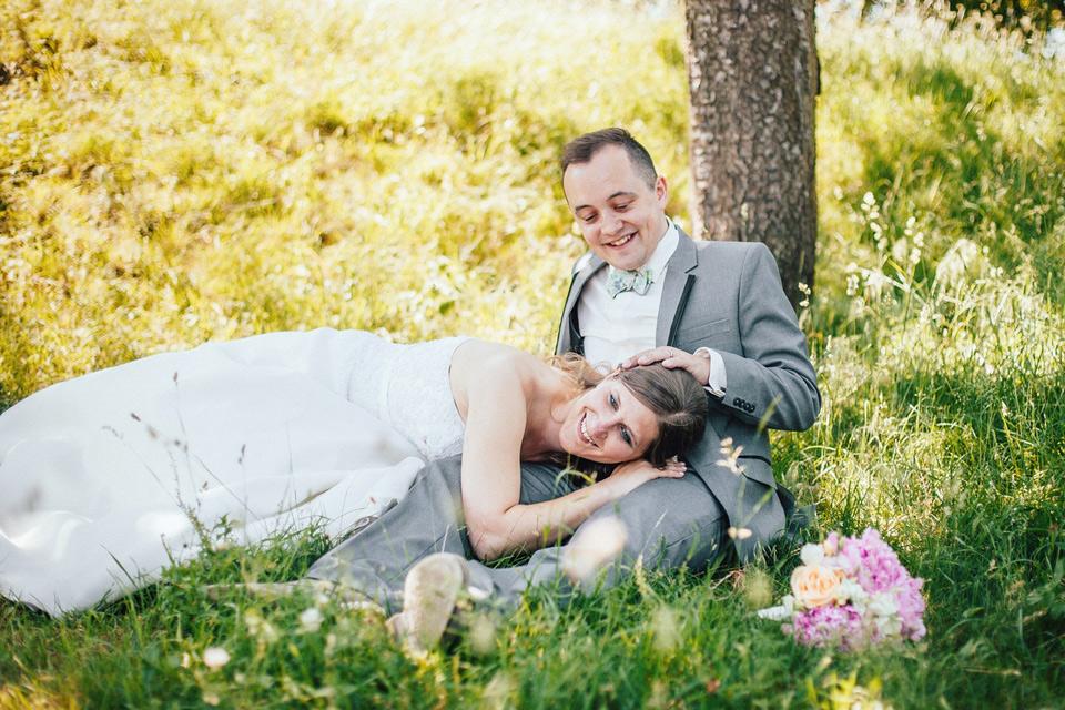 Ženich hladí nevěstu v trávě v sadu